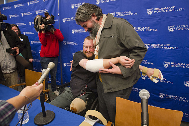 At a Brigham and Women's Hospital press conference after Will Lautzenheiser's double-arm transplantation,Will hugged his partner Angel Gonzalez with his new arms. Photo by Cydney Scott for BU Today